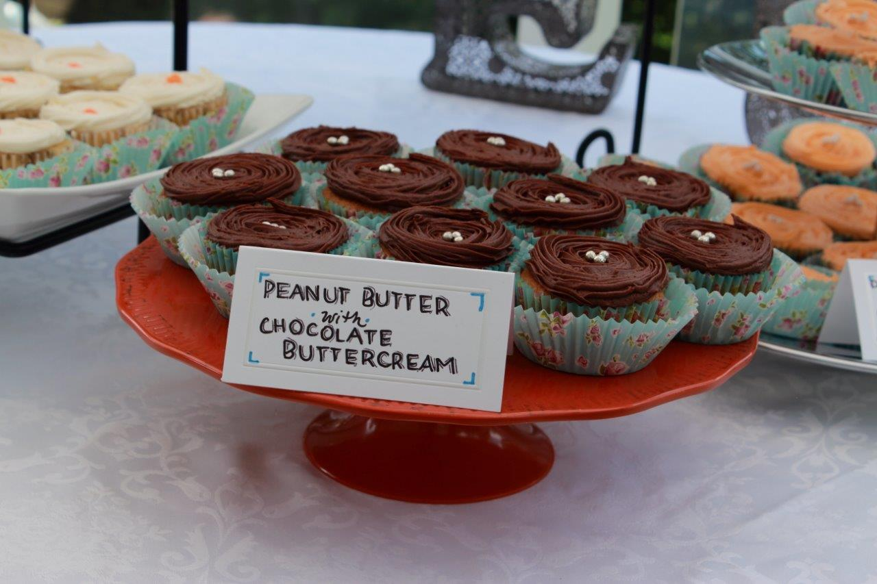 Homemade peanut butter with chocolate buttercream cupcakes on a red cake stand