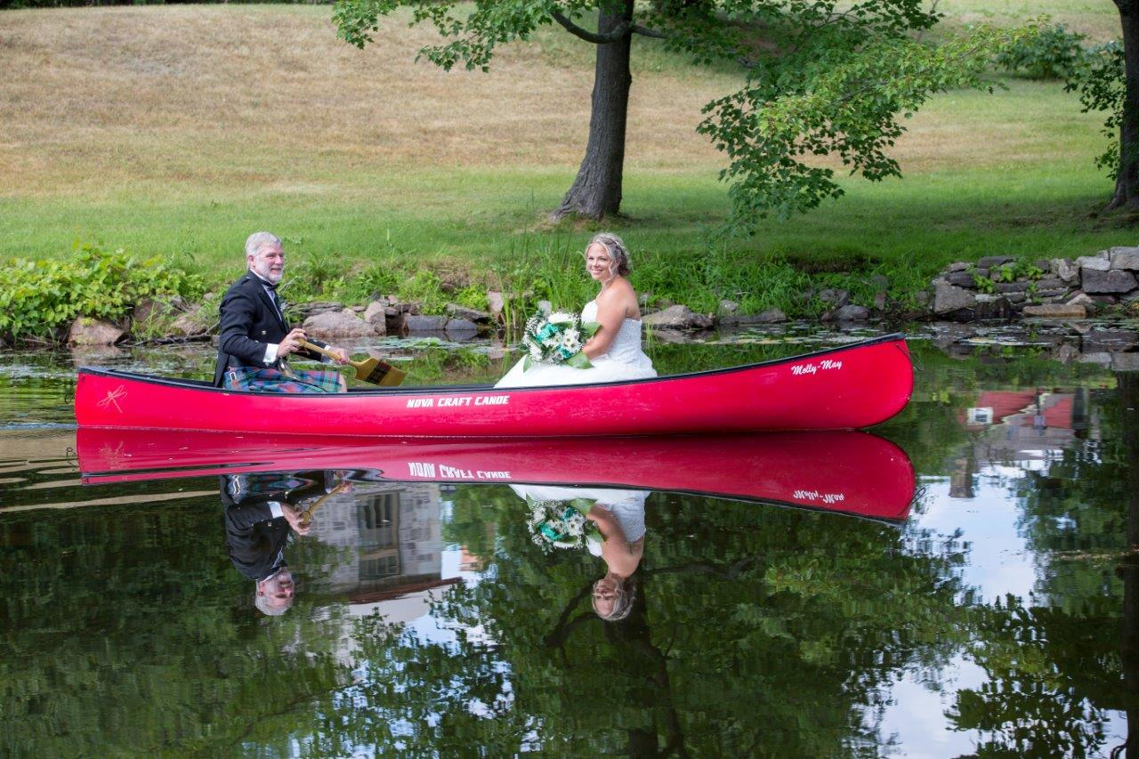 A father paddles his daughter, the bride, in a red canoe to her wedding