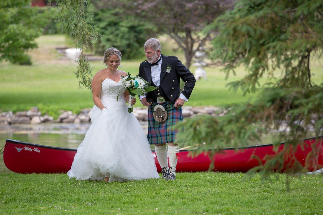 Father helps his daughter, the bride, out of a red canoe