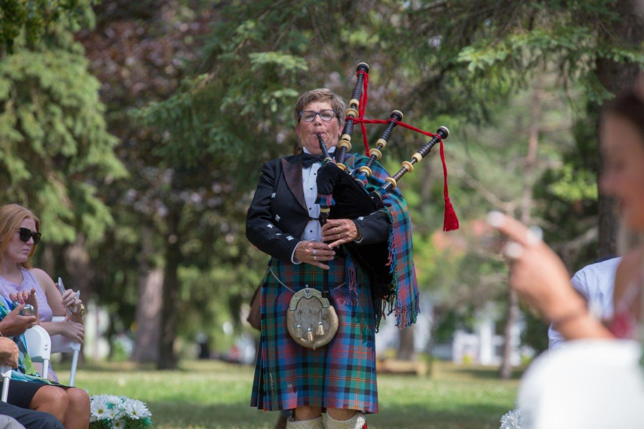 A bagpiper plays while walking down the aisle