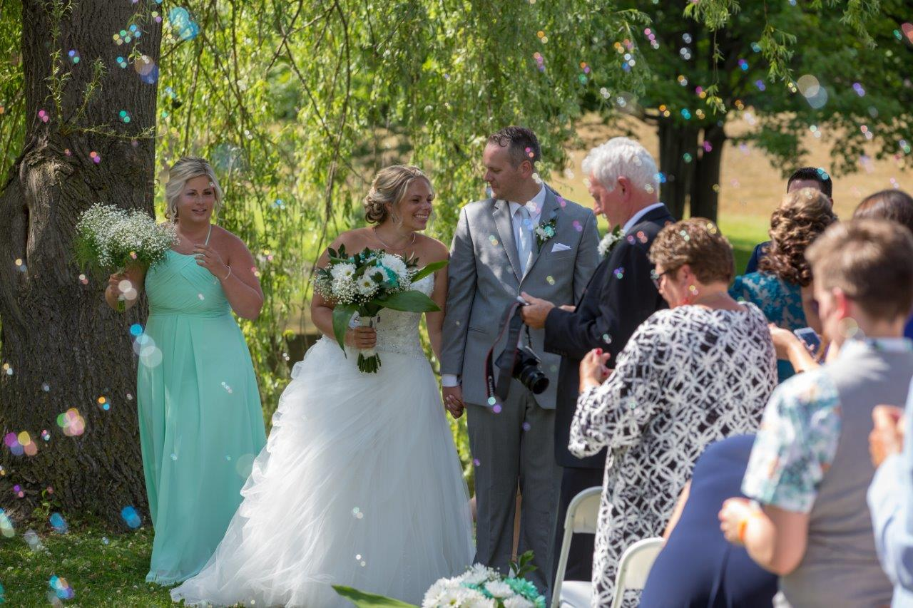 Bride and groom walk down the aisle with bubbles in the air