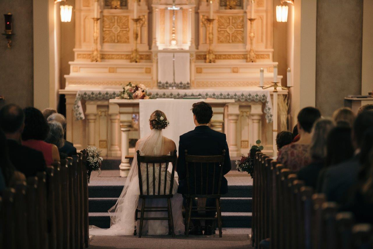Bride and groom sit together facing the altar