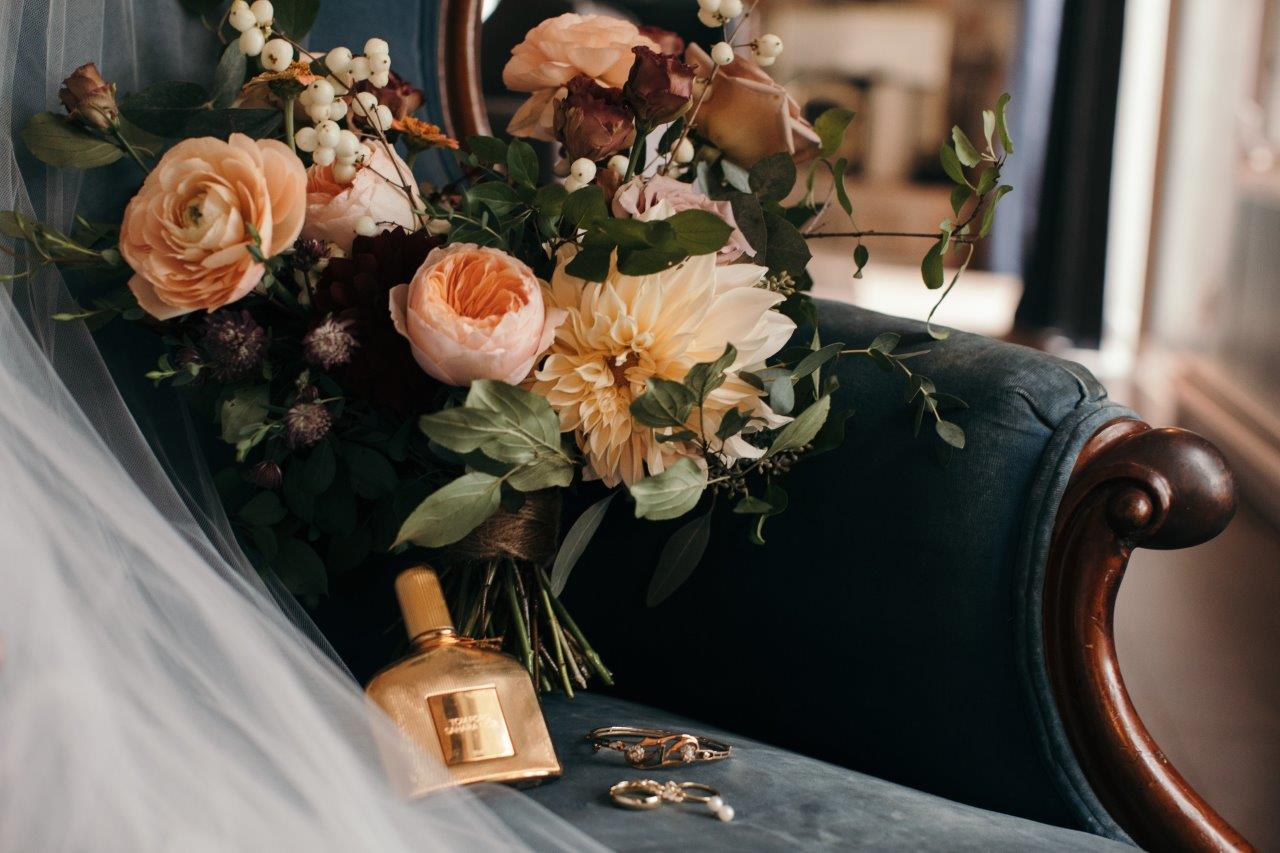 A bouquet of flowers lying on a vintage chair, on which also lie a bottle of perfume and jewellery