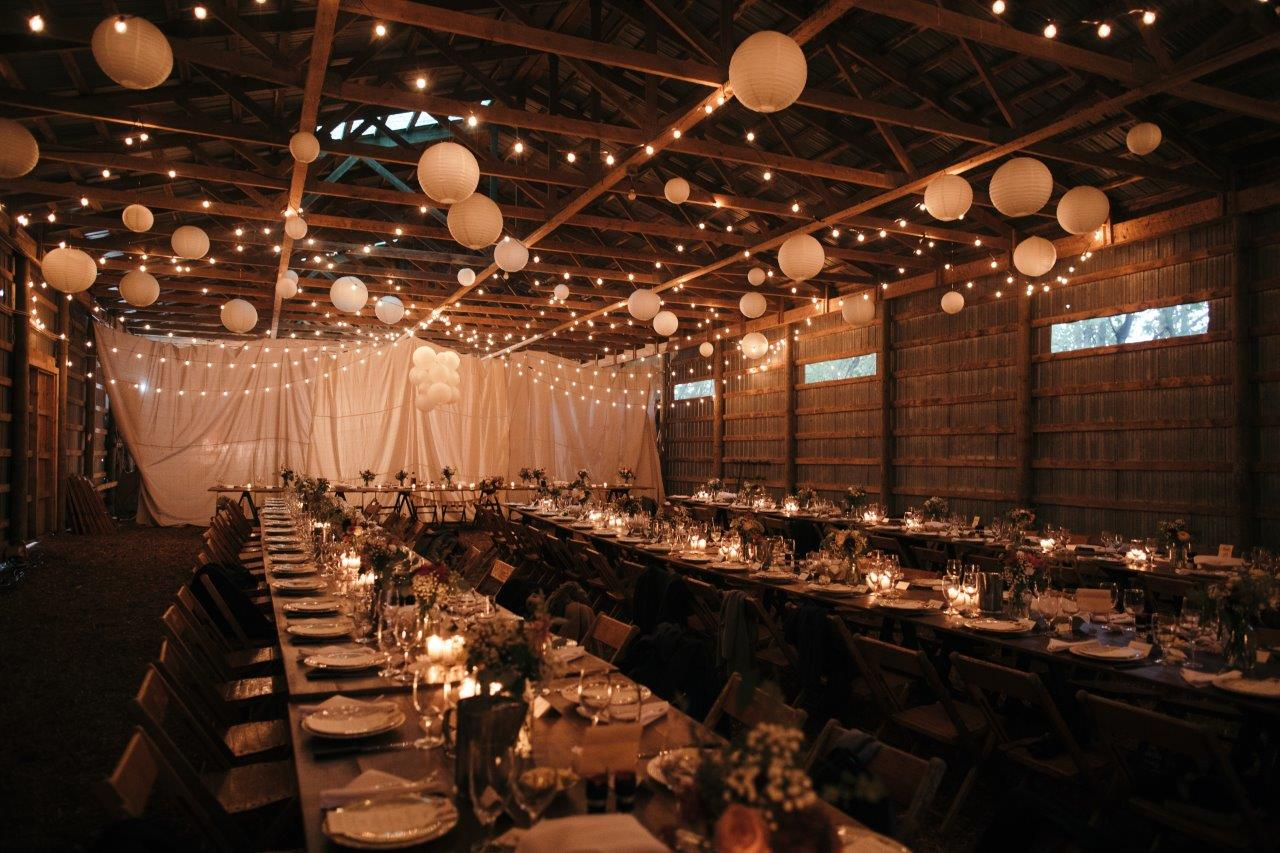 A large barn decorated with string lights and lanterns, laid out family style