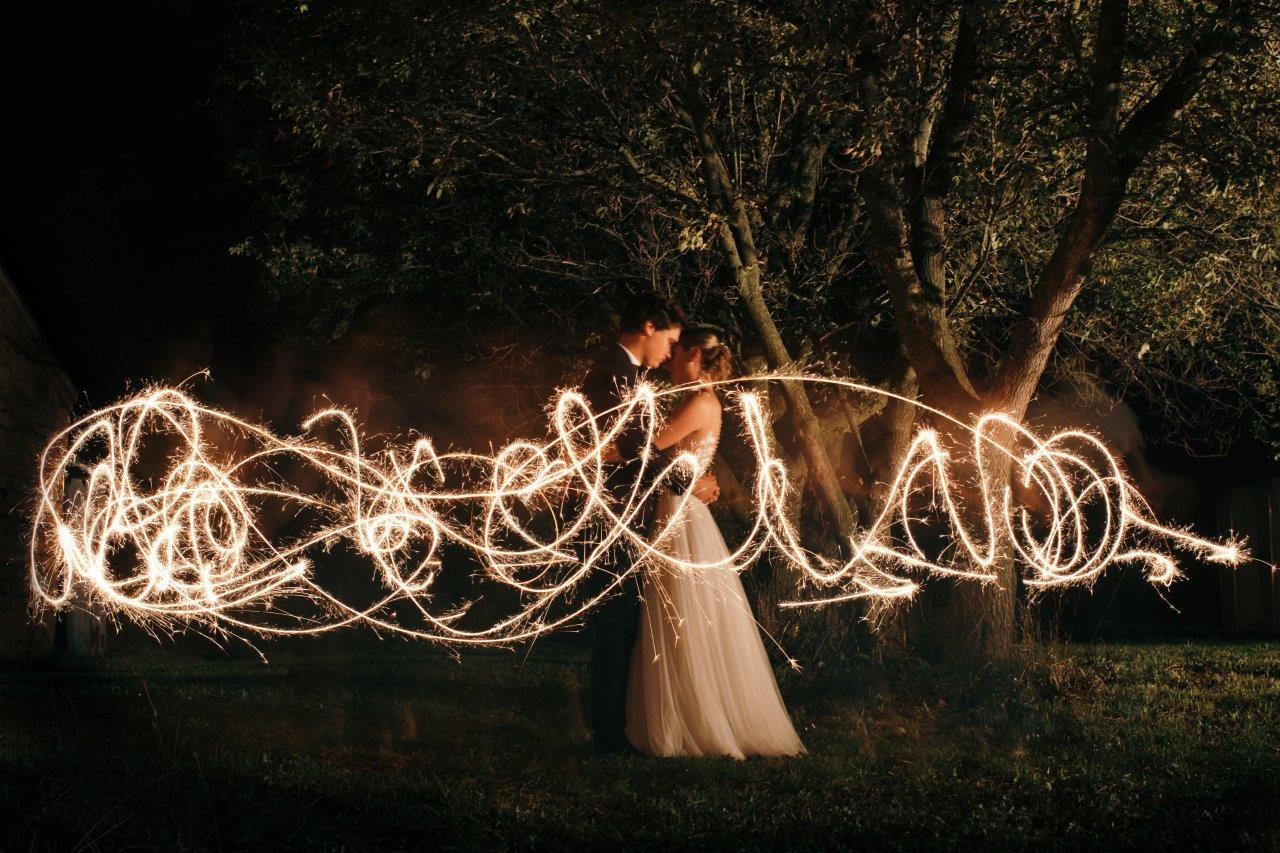 Couple kiss in the dark during a timelapse photograph overlaid with patterns drawn using a sparkler